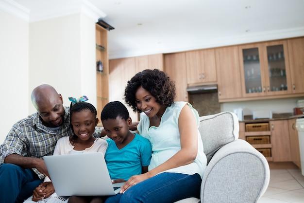 Rodzice i ich dzieci korzystają z laptopa w salonie