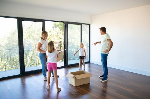 Rodzice i ich dzieci rozmawiają podczas przeprowadzki do nowego domu