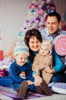 Rodzice i ich mali synowie bawią się dużymi zabawkowymi cukierkami