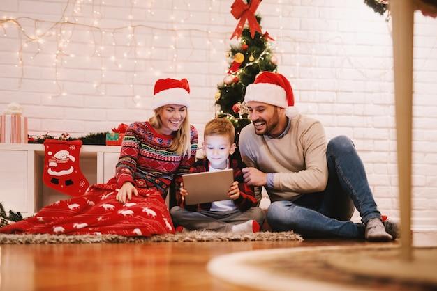Rodzice i ich syn siedzący na podłodze przed choinką. chłopiec trzyma tablet i ogląda filmy. święta bożego narodzenia koncepcja.