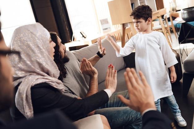 Rodzice i lekarz pokazują chłopcu znak stopu.