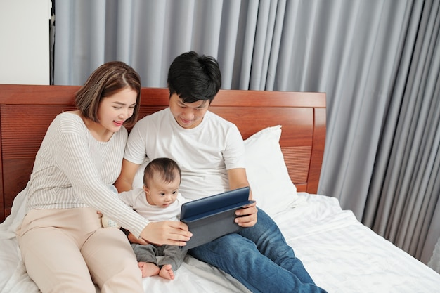 Rodzice i małe dziecko oglądają ciekawe kreskówki na komputerze typu tablet, leżąc wieczorem na łóżku