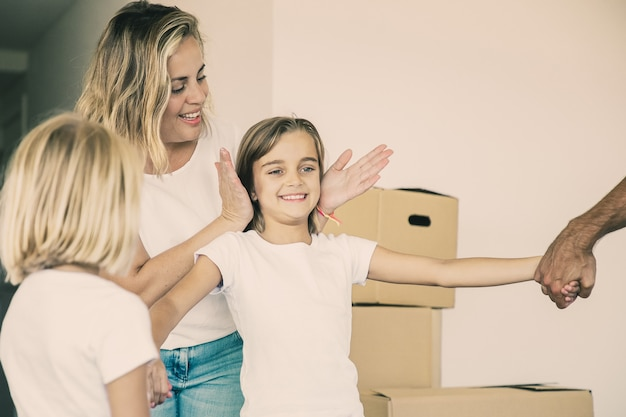 Rodzice i siostra pokazują szczęśliwej dziewczynce swoje nowe mieszkanie