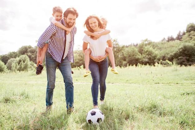 Rodzice idą łąką i trzymają dzieci na plecach. kobieta bawi się z piłką na trawie z nogą. mężczyzna i kobieta patrzą na piłkę.