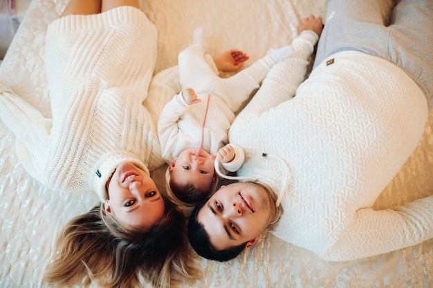 Rodzice leżą z dzieckiem na łóżku