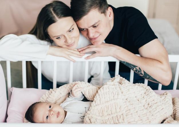 Rodzice patrzą na dziecko w łóżeczku