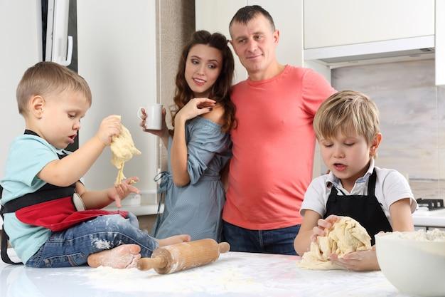 Rodzice patrzą na swoich młodych synów, którzy wyrabiają ciasto na kuchennym stole