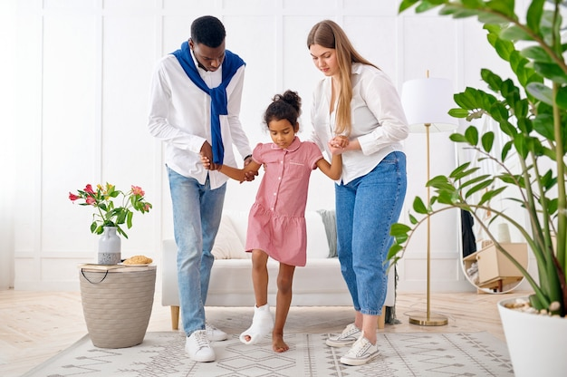 Rodzice pomagają małej dziewczynce ze złamaną nogą, wnętrze salonu. matka, tata i córeczka wspólnie radzą sobie z kłopotami, rodzicielska opieka