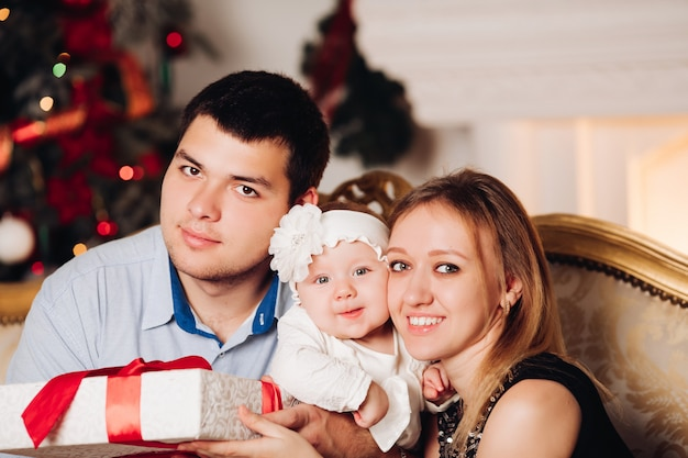 Rodzice siedzą na podłodze z dzieckiem w pobliżu choinki.