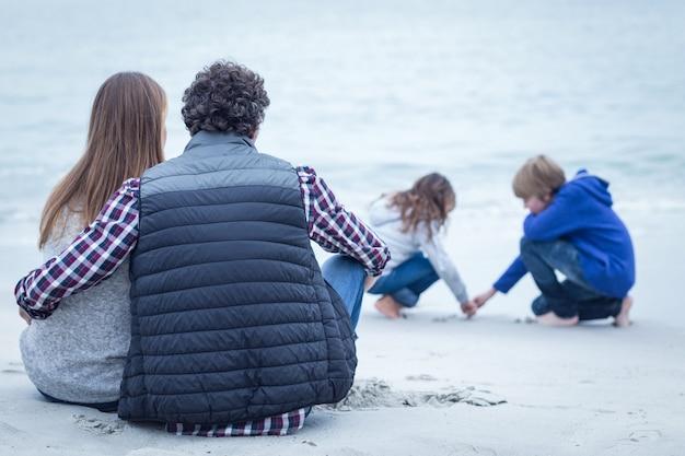 Rodzice siedzą, patrząc na dzieci na plaży