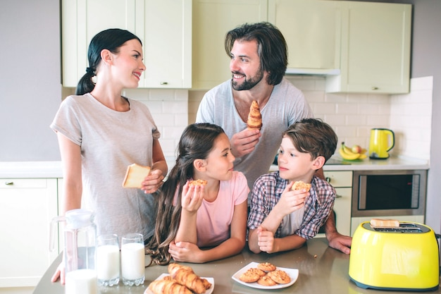 Rodzice stoją ze swoim dzieckiem. patrzą na siebie. każdy ma bułkę lub toast w rękach. oni są szczęśliwi.