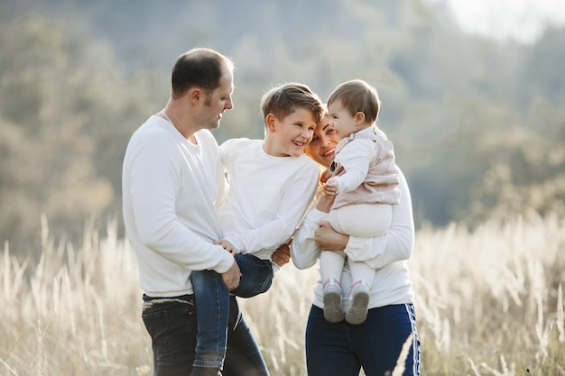 Rodzice trzymają w ręce syna i córkę i bawią się na polu pszenicy