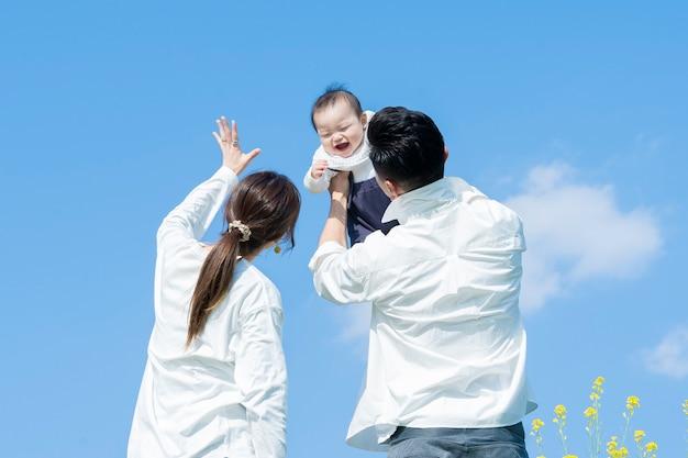Rodzice trzymający swoje dziecko wysoko pod błękitnym niebem
