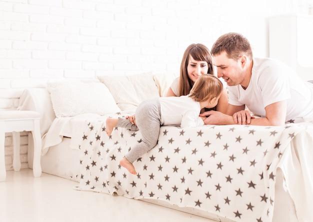 Rodzice uczą dziecko wspinać się na łóżko