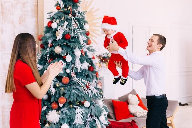 Rodzice w pobliżu choinki bawią się z małym chłopcem. odzież świąteczna.