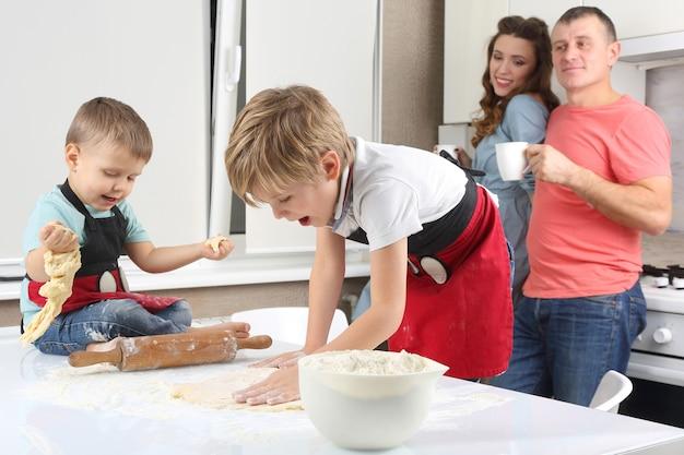 Rodzice widzą swoich synów, którzy wyrabiają ciasto na kuchennym stole