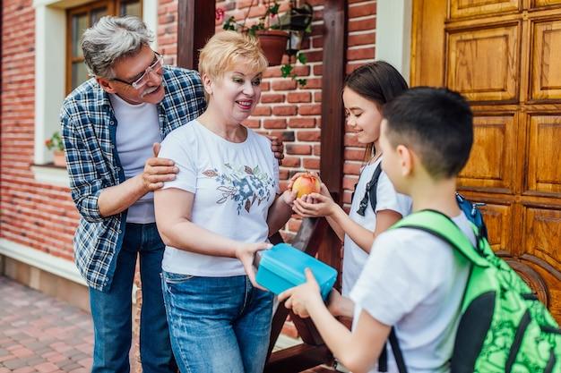 Rodzice wyślą swoje dzieci do autobusu szkolnego. daj im jeść. dziecięcy tornister na ramię.