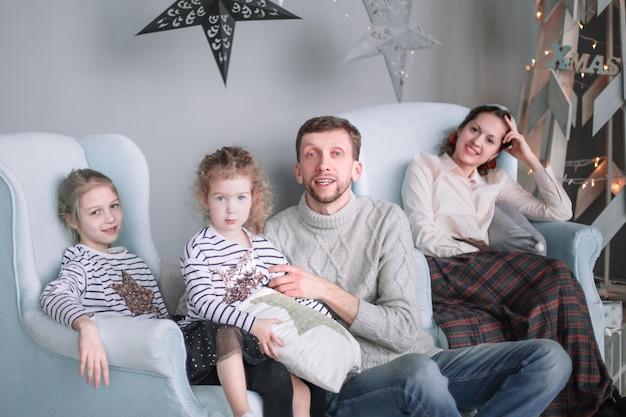 Rodzice z córeczkami siedzą w salonie w świąteczny wieczór.