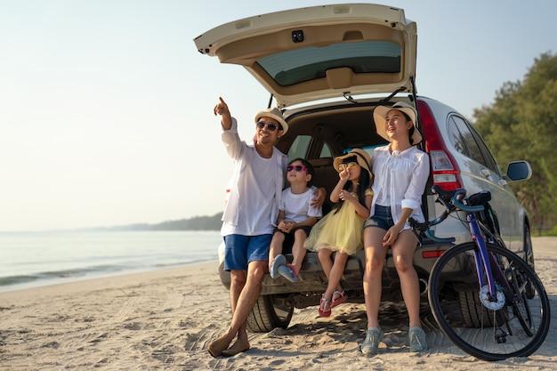Rodzice z dziećmi korzystającymi z wakacji na plaży