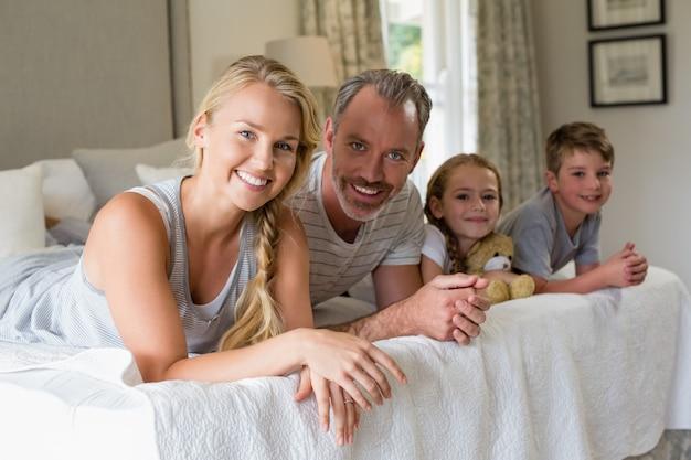 Rodzice z dziećmi leżącymi na łóżku w sypialni