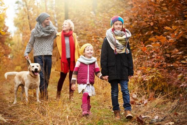 Rodzice z dziećmi spacerującymi po jesiennym lesie