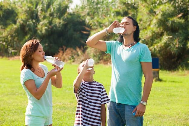 Rodzice z nastolatkiem piją z butelek
