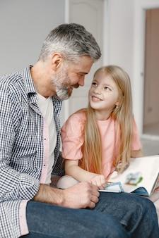 Rodzicielstwo. ładna dziewczyna siedzi z dziadkiem w sypialni. wspólne czytanie książki.