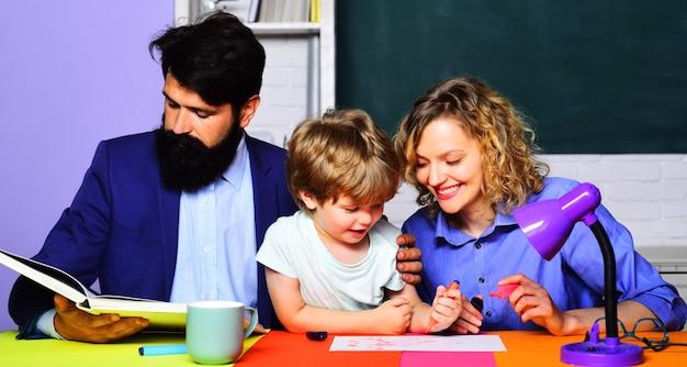 Rodzicielstwo. rodzice pomagają synowi odrabiać lekcje. szkoła rodzinna. pierwszy raz do szkoły.