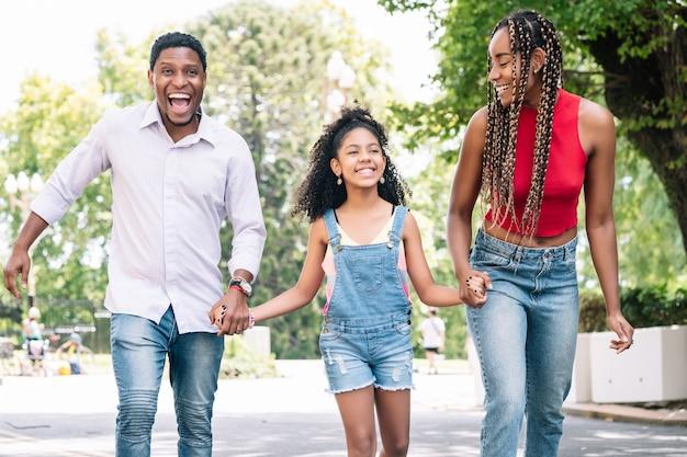 Rodzina afroamerykanów dobrze się bawi podczas wspólnego spaceru na ulicy.
