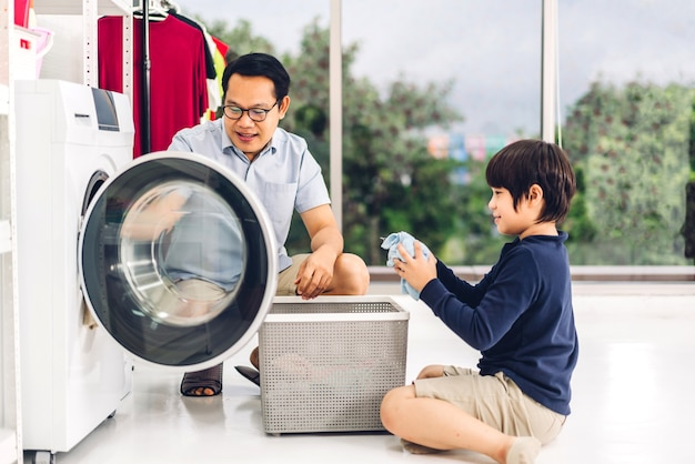 Rodzina azjatycki ojciec i dziecko syn syn bawią się, wykonując prace domowe, robiąc pranie brudnych ubrań do pralki razem w pralni w domu