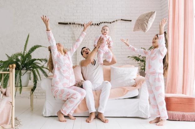 Rodzina bawi się w domu i rzuca poduszki w powietrze