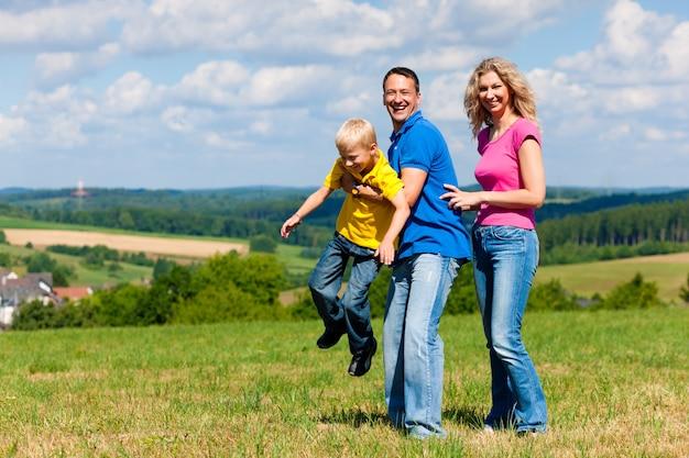 Rodzina bawić się na łące w lecie