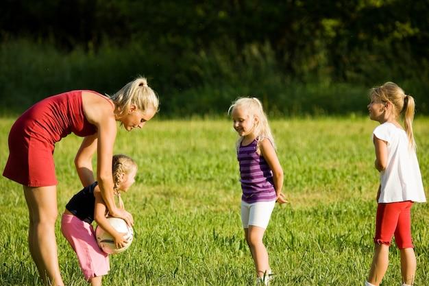 Rodzina bawić się piłkę nożną w trawy polu