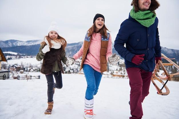 Rodzina biegnąca przez zaśnieżone wzgórza