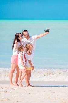 Rodzina bierze selfie zdjęcie na plaży. rodzinne wakacje na plaży