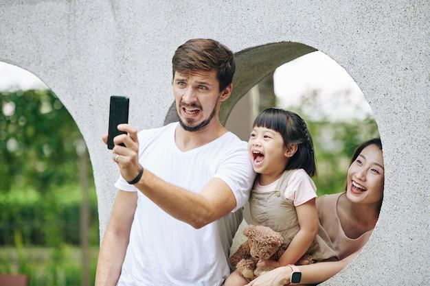 Rodzina biorąc śmieszne zdjęcie w parku