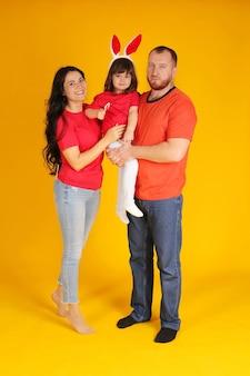 Rodzina brunetka dziewczyna facet czerwona broda córka na głowie królik różowe uszy przytulanie