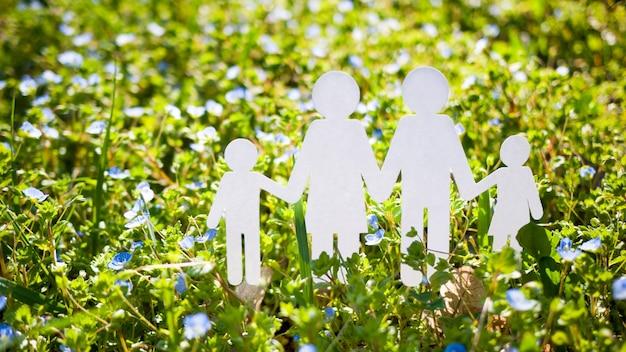 Rodzina cięcia papieru na zielonej trawie
