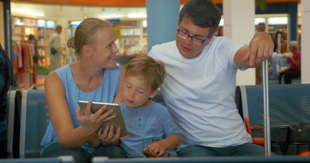 Rodzina czeka na wyjazd z komputerem typu tablet