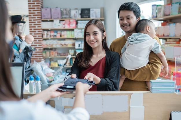Rodzina dokonująca płatności w sklepie dla dzieci kartą kredytową w kasie