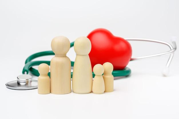 Rodzina drewniane postacie mężczyzn na tle czerwonego serca i stetoskop, pojęcie ubezpieczenia zdrowotnego, z bliska
