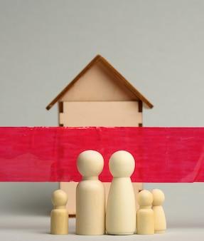 Rodzina drewnianych figurek i drewniany dom za czerwoną wstążką na szarej powierzchni. koncepcja kwarantanny, blokada podczas pandemii i epidemii. zostań w domu