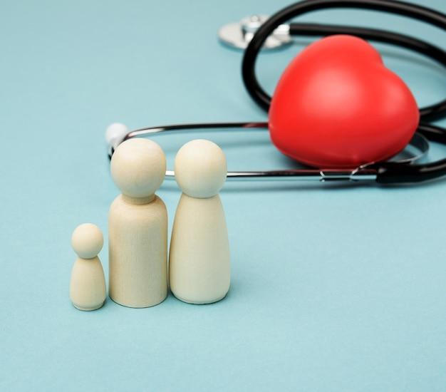 Rodzina drewnianych postaci mężczyzn na tle czerwonego serca i stetoskopu, pojęcie ubezpieczenia zdrowotnego, z bliska