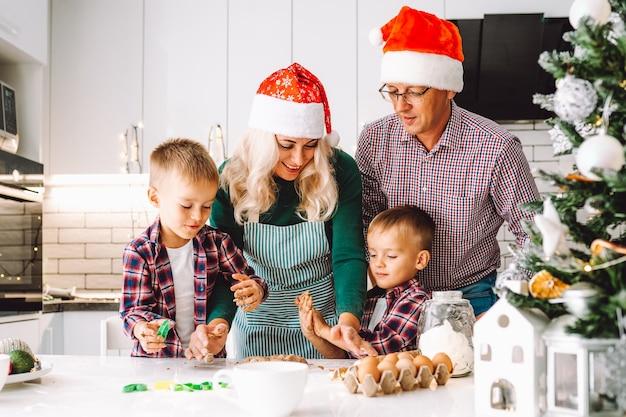 Rodzina dwóch bliźniaków chłopców i rodziców w wieku przygotowujących ciasteczka na boże narodzenie lub nowy rok w jasnej kuchni w czapkach mikołaja.