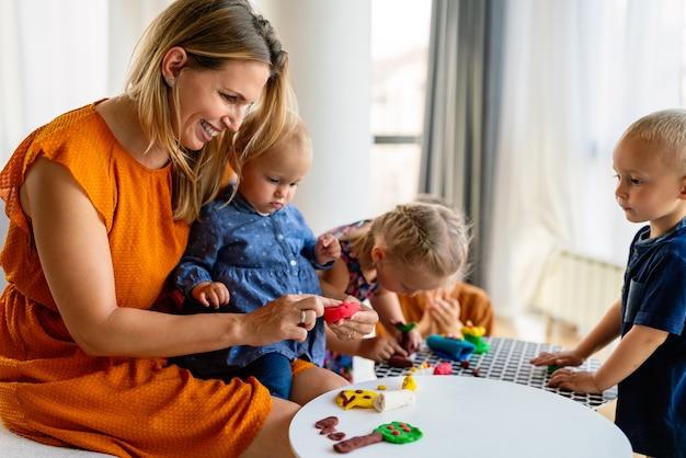 Rodzina, dzieci, edukacja, koncepcja szczęścia. matka uczy dzieci w wieku przedszkolnym robienia przedmiotów rzemieślniczych.