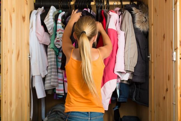 Rodzina, dziecko przed szafą lub garderobą