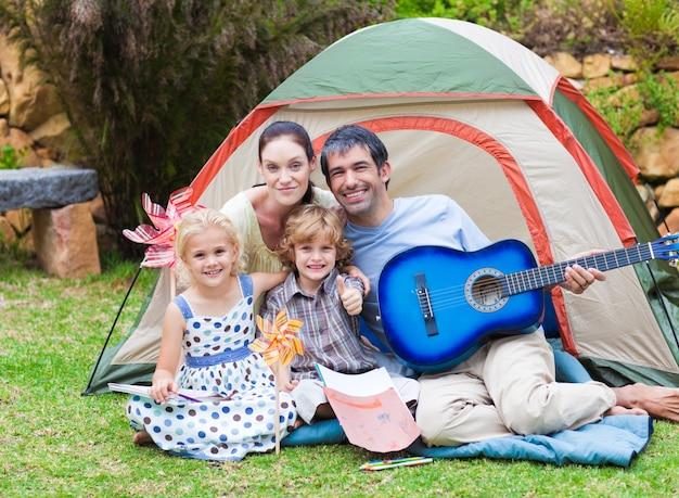 Rodzina gra na gitarze w namiocie