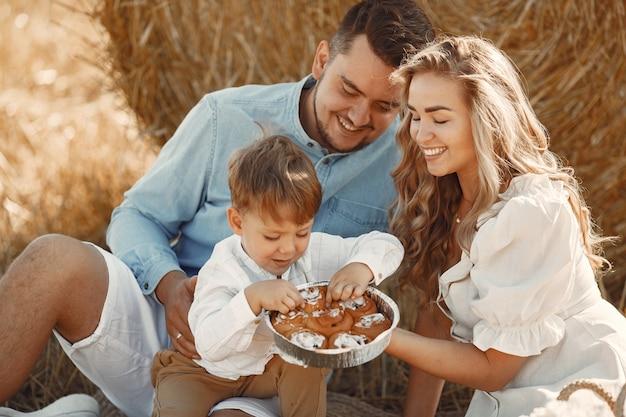 Rodzina gra z synkiem w polu pszenicy na zachód słońca. ludzie na pikniku. rodzina spędza razem czas na łonie natury.