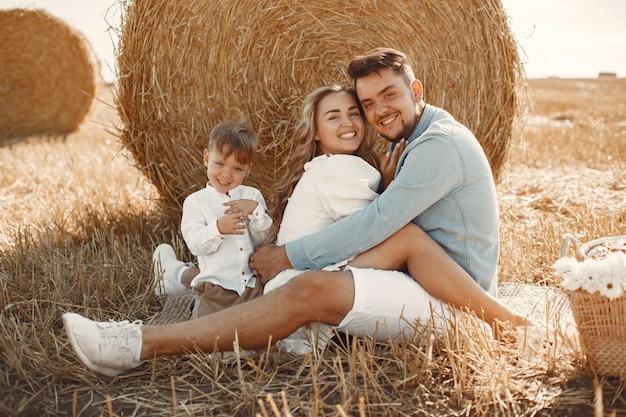 Rodzina gra z synkiem w polu pszenicy na zachód słońca. pojęcie wakacji letnich. rodzina spędza razem czas na łonie natury.