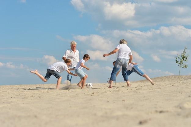Rodzina grająca w piłkę nożną na plaży w letni dzień